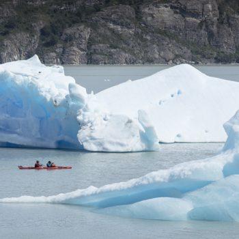 kayaking on grey lake among icebergs